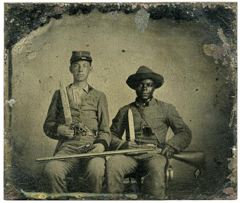 Sergeant A.M. Chandler of the 44th Mississippi Infantry Regiment, Co. F., and Silas Chandler, family slave, with Bowie knives, revolvers, pepper-box, shotgun, and canteen, circa 1861-1863. Source: Library of Congress.