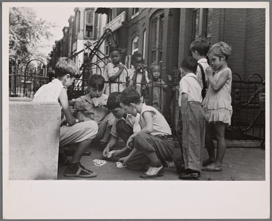 Children playing cards in front yard in slum area near Union Station. Section inhabited by both whites and Negroes. Washington, D.C., Carl Mydans, September 1935