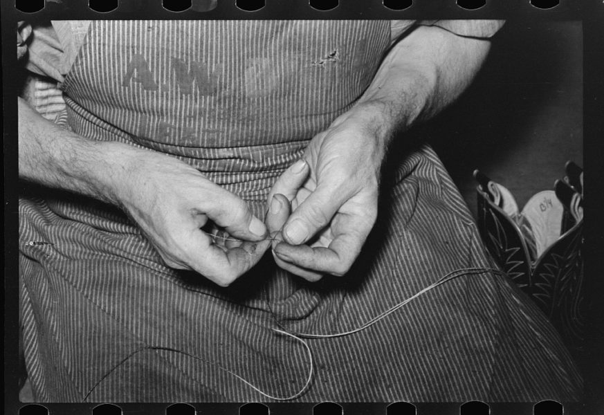 Lee, Russell, photographer. Threading a needle with waxed thread. Bootmaking shop, Alpine, Texas. May, 1939. Image. Retrieved from the Library of Congress, https://www.loc.gov/item/fsa1997026143/PP/. (Accessed September 19, 2016.)